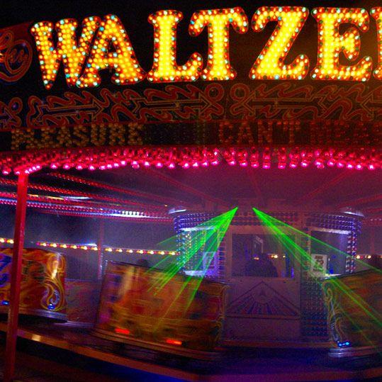 Waltzer ride lit up at a funfair