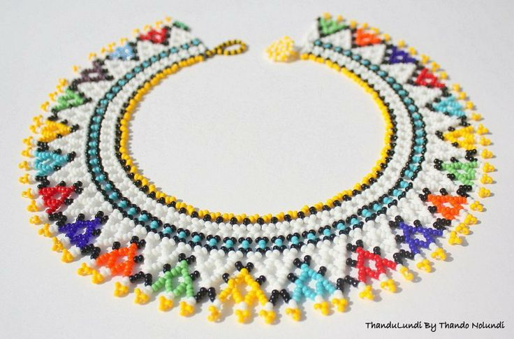 Bright multi-coloured traditional Zulu neck collar with beaded hook and flat button-like fastening. Very eye catching. And truly stands-out when worn with most outfits.Intricately handcrafted in South Africa using colourful glass beads. Inner neck length approx. 40cm Note: each neck collar is unique and individual.