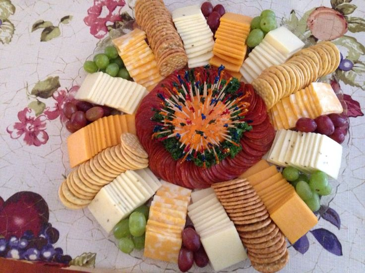 Cheese and cracker platter. An orange cut in half secures the toothpicks.