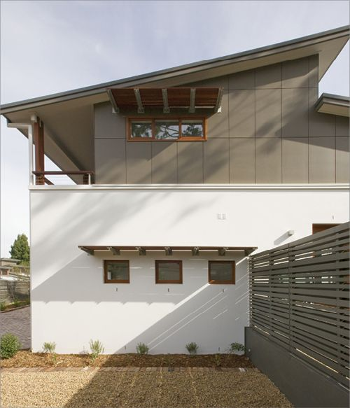 The east-facing side of a house, which has had fixed awnings fitted over its windows in order to provide extra shade.