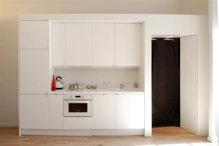 La cuisine prend le sas d'entrée dans son volume. Un rideau noir a été installé et sert de sas devant la porte palière. / ©Simon Vanquaethem