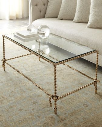 """Brass tassle rope Coffee Table  at Horchow. We've never seen anything quite like this gorgeous table made to look just like rope, complete with knots and tassels at the corners. Handcrafted of iron. Antiqued-gold finish. Includes a glass top. 44""""W x 25.75""""D x 19""""T."""