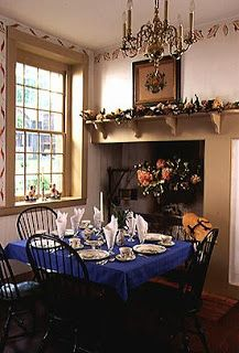 A TRADITIONAL DINING ROOM WITH WINDSOR CHAIRS, A STENCILED BORDER ON THE  WALLS, A