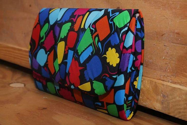 Clutch desenvolvida a partir de tecido reaproveitado de guarda chuva, aplicando o conceito de upcycling.