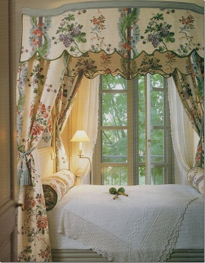 Canopy bed with scalloped detail and bolster pillows