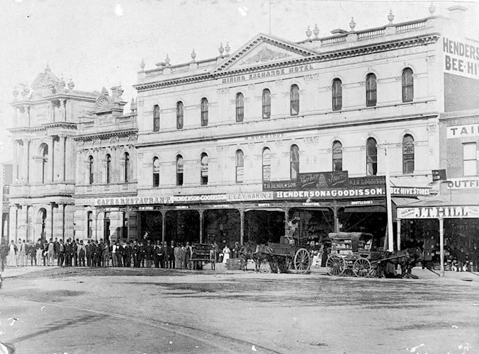 The Exchange Hotel. On the right, Henderson and Goodisson Beehive Stores, a cafe and restaurant on the left There is a horse-drawn van and a horse and cart as well as a large group of people in front of the hotel. Pall Mall, Bendigo, Victoria, Australia, 1890 W H Robinson Studio, 1890