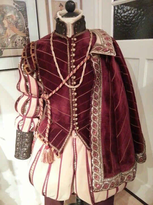 16th Century renaissance suit, from red and gold velvet, slashed and lined with gold silk jacquard. Suit consists of a doublet with detachable sleeves with leather cuffs and collar, trunk hose, cloak, chemise with redwork embro and bonnet (not in picture). Costume maker: Angela Mombers.