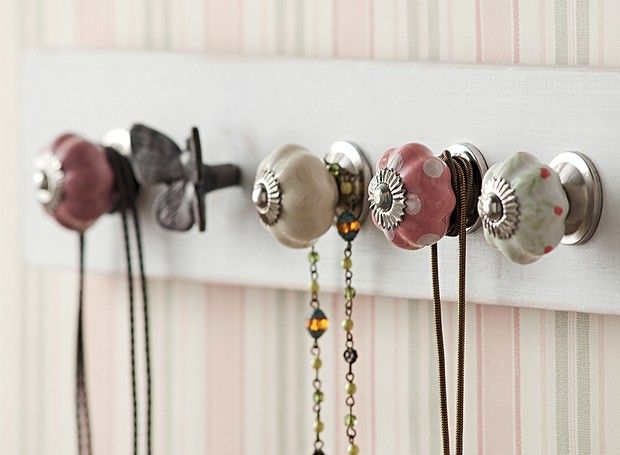 Presos a uma régua de madeira, os puxadores de porcelana e o de ferro em forma de borboleta deixam os colares organizados e à mão (Foto: Luís Gomes)
