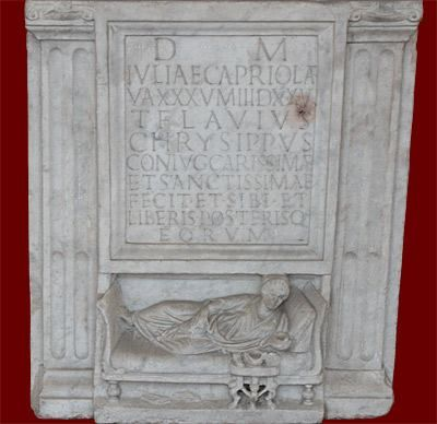 Cinerary alter of Julia Capriola; from the Esquiline graveyard, Rome, Trajanic period (98-117 CE). Julia Capriola is shown reclining on a banqueting couch (lectus) with a pillow behind her left elbow. She holds a cup as if to drink; before her is a small table with food. Her sandals are carelessly tossed beneath the couch, and she luxuriously stretches the toes of her bare foot.