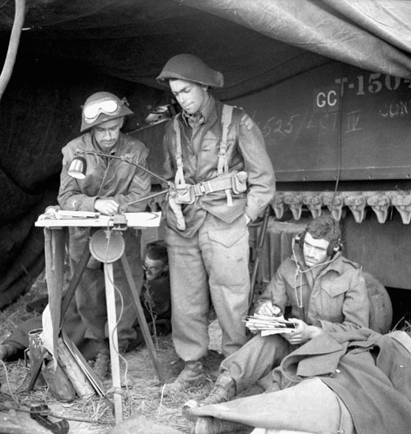 Unidentified personnel of the Canadian Armoured Corps (C.A.C.) using wireless signal information to plot enemy movements in the Normandy beachhead, France, 6 June 1944.