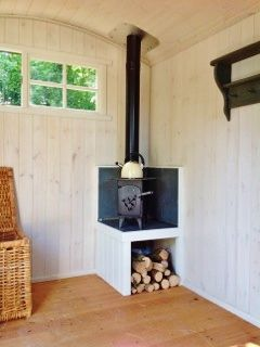 Fitted Wood Burner on a raised hearth in an Ashwood Hut.