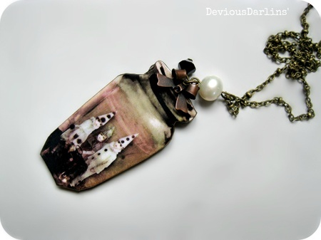 Conserved Memories.. Gorgeous and eerie laser cut wood necklace, with a resin covered image of children in vintage clown costumes <3 From Devious Darlins'..