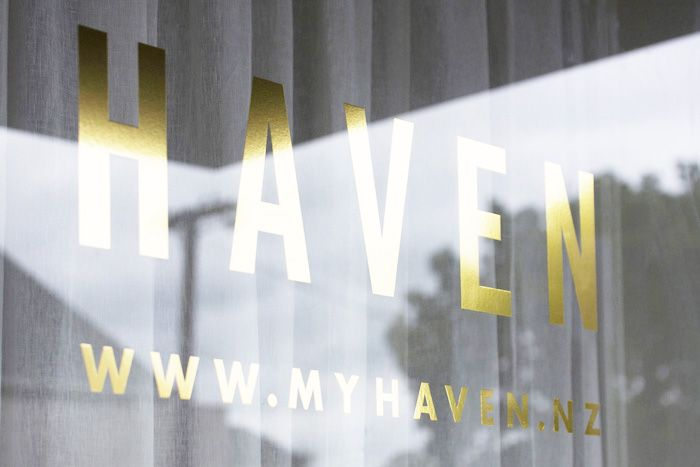 Gold signage backed by white sheer curtains masking the waiting area beyond. | Haven (373 Dominion Road, Auckland) | Photo by the talented Jeremy Toth | Fit out by Material Creative.