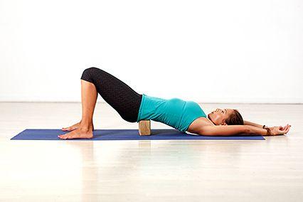 Полумостик с поддержкой    Лягте на спину, колени согните, стопы поставьте на пол. Руки расположите вдоль корпуса. Положите под поясницу кирпич для йоги (или книгу) и вытяните руки за головой. Равномерно распределите вес тела между стопами, лопатками и поясницей. Дышите в спокойном темпе.
