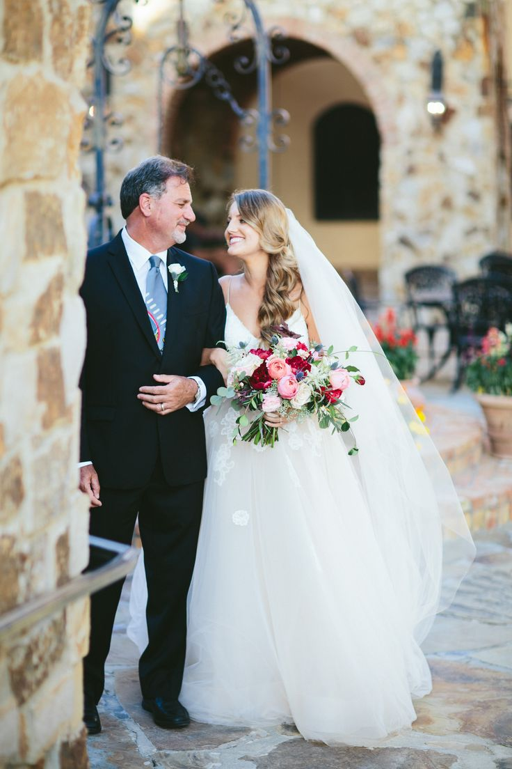 the bride and her father share a moment before heading down the aisle. the bridal bouquet is a loose and lush bouquet of burgundy, pink, peach, blush and white flowers mixed with textures, vines and greenery.