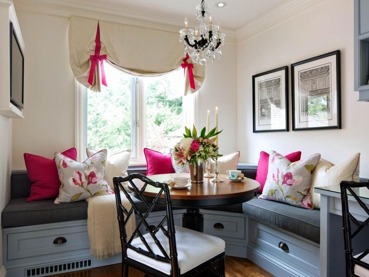 This breakfast nook features steel-blue banquette seating with dark gray cushions and pink floral pillows. Pink bows on the white window valance and the black and crystal chandelier lend a romantic touch to the space.