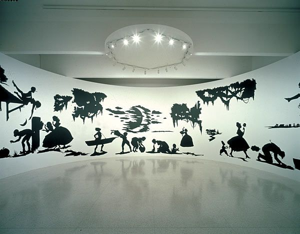 """Kara Walker  African-American artist Kara Walker, a pioneer in the utilization of the """"stereotypical grotesque,"""" uses violent and hyper-sexualized silhouetted images  ante-Bellum South to re-stage the myths of racist lore. The caricatures are elegant in their execution and repulsive in their depictions. A criticism of the enduring nature of racist imaginings."""