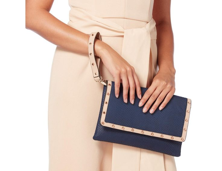 This statement studded clutch bag makes for an edgy evening wear staple. Featuring an inside pocket, optional chain strap and magnetic snap closure. This would look great with smart jeans, statement top and matching heels.