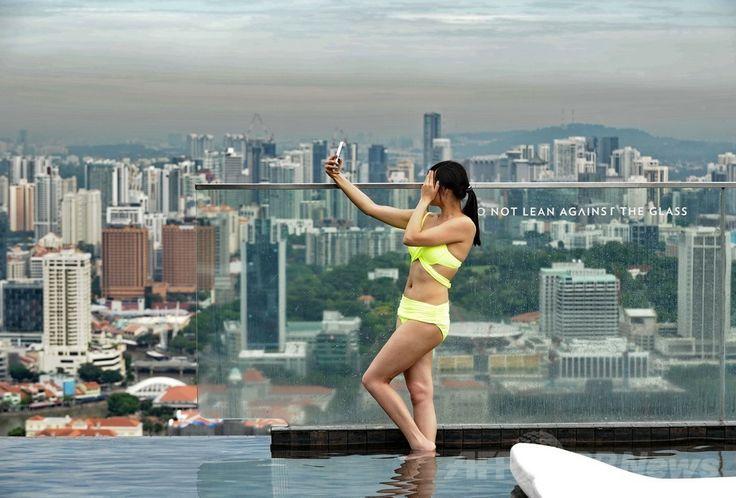 シンガポールの高級リゾートホテルのマリーナ・ベイ・サンズ(Marina Bay Sands)の屋上にある「インフィニティープール(Infinity Pool)」でくつろぐ女性(2014年5月20日撮影)。(c)AFP/ROSLAN RAHMAN ▼23May2014AFP 高級ホテルの屋上プールで景色を満喫、シンガポール http://www.afpbb.com/articles/-/3015704 #Marina_Bay_Sands #Infinity_Pool