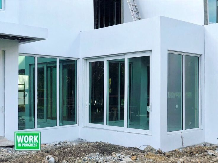 Installation of impact-resistant windows and doors in Pinecrest, Florida.  The picture features windows and sliding glass doors in white finish, with clear glass, with LowE coating for improved energy efficiency.