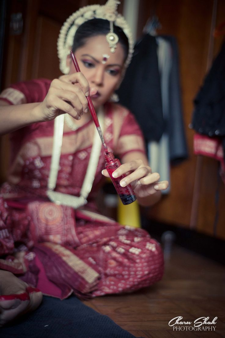Odissi dancer applying alta backstage