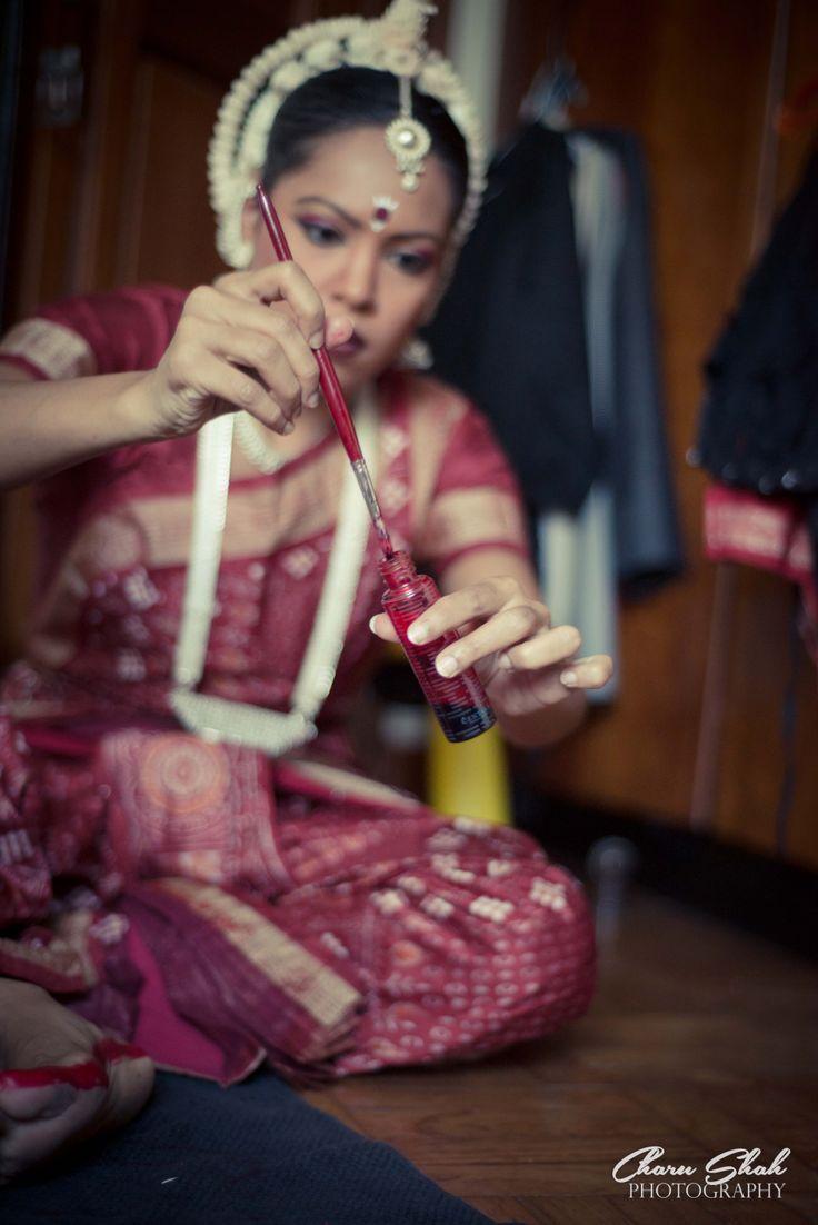 Odissi dancer applying alta backstage