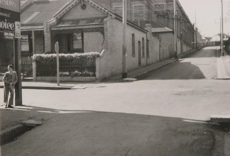 19 September 1949 Angel Street, looking north, at the corner of Newman Street. Corner store advertising Kaiora fruit juices and Keens Mustard. Terrace houses and tram depot are on the left