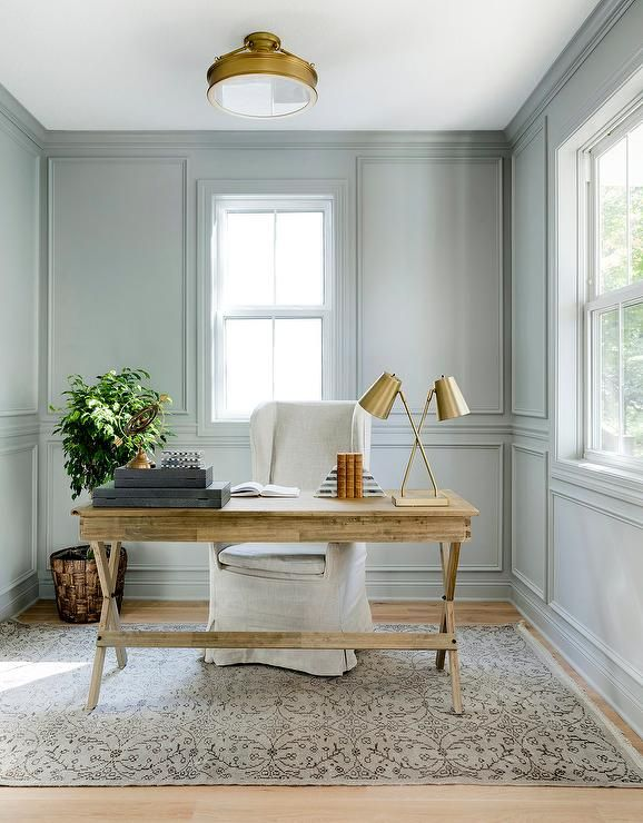 Bria Hammel Interiors - You'll be comfortably working away in this gorgeous home office featuring a linen wingback chair placed on a beige wool rug at a wood x-based desk lit by a brass 2 light task lamp and a brass semi flush mount.