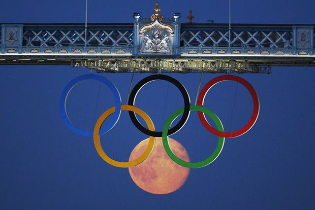 The full moon rises through the Olympic Rings hanging beneath Tower Bridge during the London 2012 Olympic Games - Luke MacGregor
