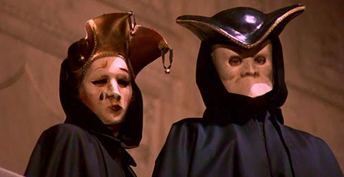 A couple wearing Venetian masks slowly turn towards Bill and nod in a very creepy matter