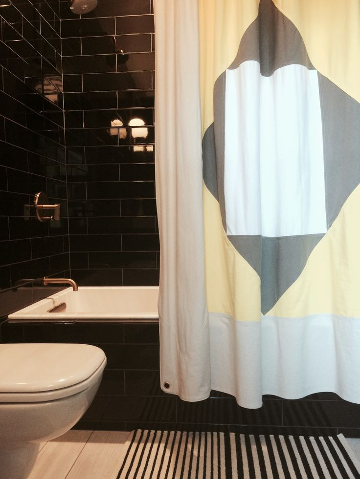 Added a bit of bohemian to this black, white, & brass bathroom & kept it kid-friendly by using a woven kilim bath mat & quilt-inspired cotton canvas shower curtain.