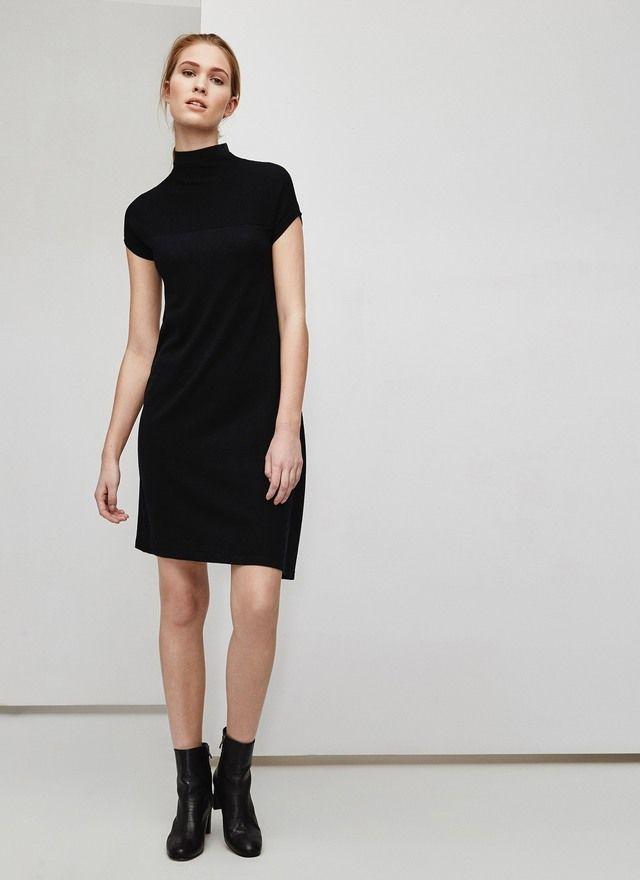 Vestido negro en punto grueso de lana merino, muy suave al tacto. Corte de cintura baja con vuelo asimétrico, cuello perkins y manga corta caída.