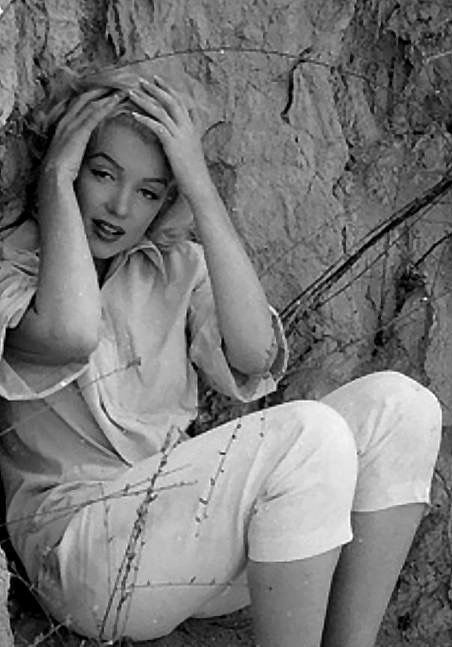 Marilyn Monroe. Laurel Canyon, rock sitting. Photo by Milton Greene, 1953.