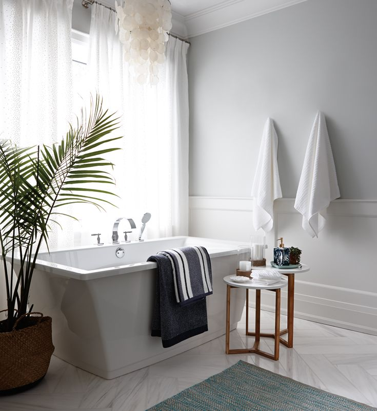 Colour and texture make a white bathroom inviting nesting tables white and andy towels clean lines and a hit of greenery