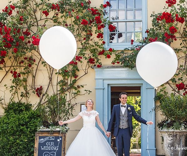 Bride and groom with balloons at South Farm wedding venue in Cambridgeshire   CHWV