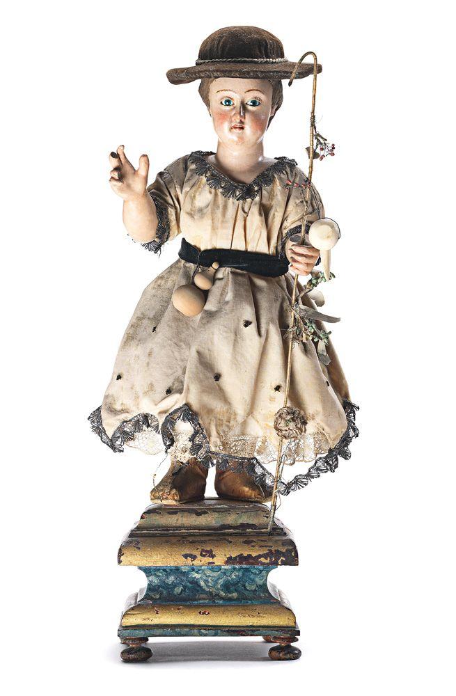 Menino Jesus peregrino, escultura em madeira pintada, séc. XVIII/XIX. O Menino Jesus usa vestido debruado a fio metálico, junto com os atributos dos peregrinos, o chapéu de abas largas, a vara de caminheiro e a cabaça. Assente sobre peanha em madeira entalhada e policromada. Olhos em vidro.  Alt. aprox. Menino: 35,5 cm.; Alt. aprox. total: 46,5 cm.