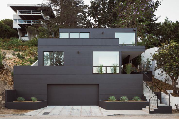 contemporary small lot architecture, black concrete siding, hillside lot
