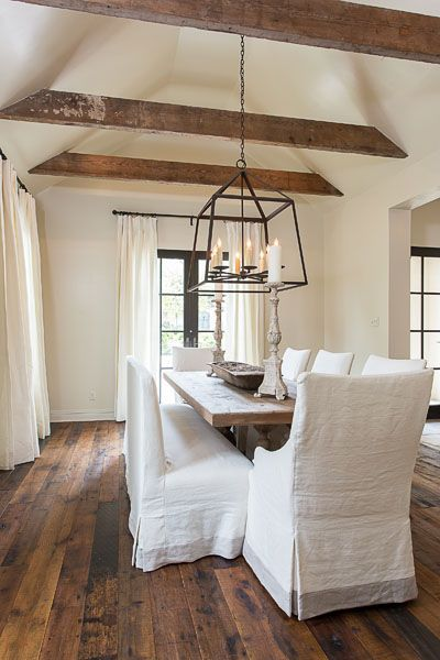 Chic rustic dining room with vaulted ceiling accented with wood beams as well as creamy white curtains on iron drapery rods covering black French doors.