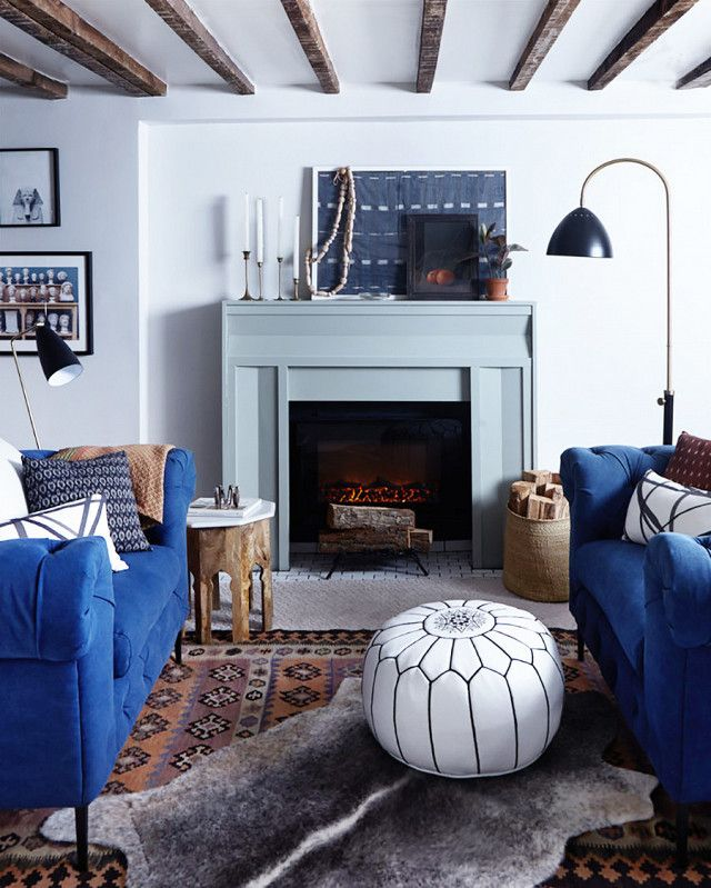 Cozy living space with exposed ceiling beams, a painted fireplace, matching blue sofas, and layered rugs