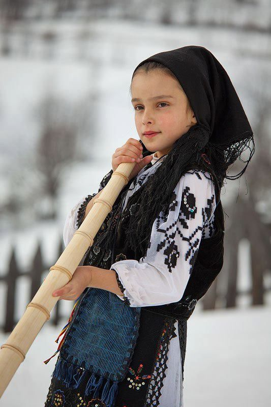 Romanian folk tradition - young woman in traditional costume playing the musical instrument bucium
