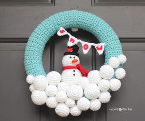 Christmas Crochet Patterns - This pic for inspiration. Yarn snowballs on a yarn-wrapped wreath, maybe with crocheted snowflakes at the top? Maybe no figure if that looks snowy enough.