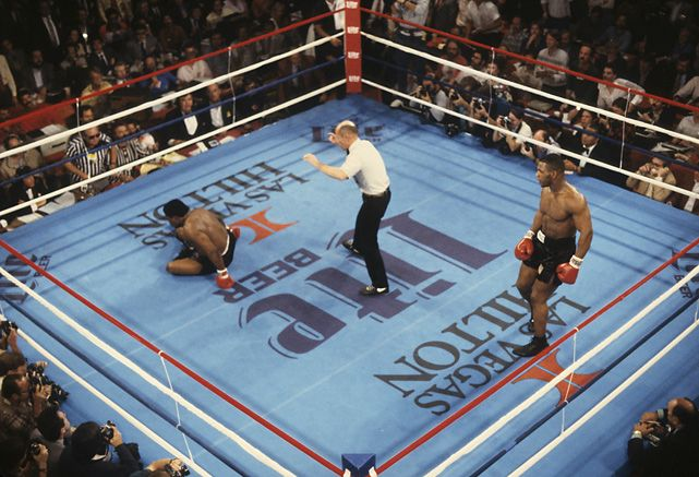 Mike Tyson watches as referee Mills Lane counts out Trevor Berbick during their 1986 fight in Las Vegas. Tyson won the fight to become the youngest world heavyweight champion in boxing history (20 years, four months).