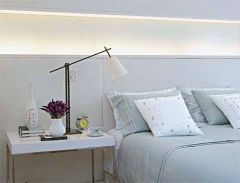 Para valorizar a cabeceira da cama do tipo box, criou-se um painel de madeira revestido de couro ecológico branco. No nicho que se forma no meio, a luz embutida proporciona um clima mais intimista ao ambiente. Projeto de Marcelo Rosset.