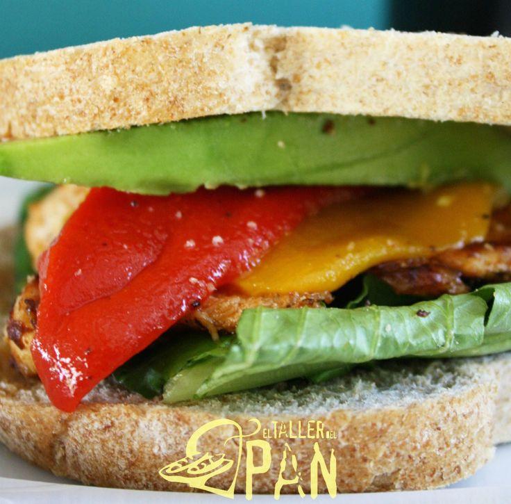 Sándwich con pan de miga integral, aguacate, pimentones rostizados, pollo, lechuga y cebollas caramelizadas