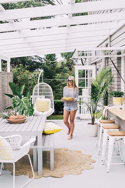 The perfect summer deck with a hanging chair, rush matting, potted palms and the piece de resistance - the serving bar open to the kitchen