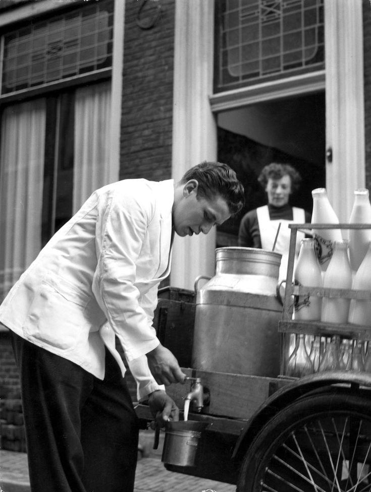 Een melkboer aan huis tapt melk in een melkkannetje vanuit een grote melkkan achterop zijn kar, onder toeziend oog van de vrouw / klant in de deuropening. Nederland, Haarlem, Ursulastraat, 1956.