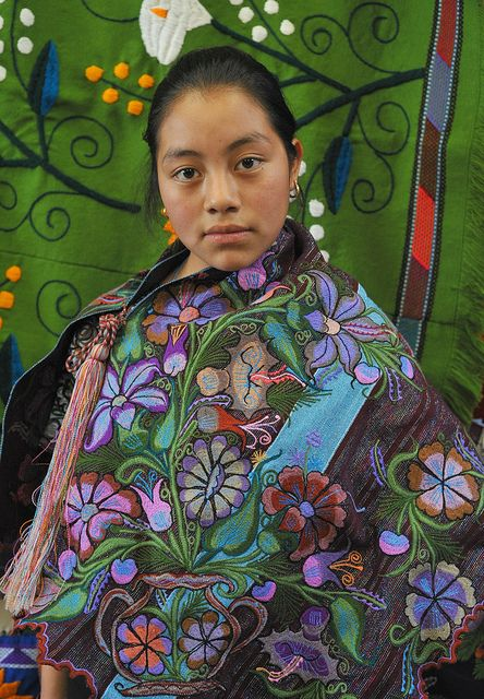 A young Maya woman wears a cape embroidered with flowers. Chiapas, Mexico