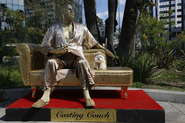 """A dog named """"Sassi"""" sits next to a golden statue of a bathrobe-clad Harvey Weinstein, seated atop a couch on the sidewalk along Hollywood Blvd., in Los Angeles Thursday, March 1, 2018. The piece, titled """"Casting Couch,"""" is a collaborative effort between a Los Angeles street artist known as Plastic Jesus and Joshua """"Ginger"""" Monroe, creator of the nude Donald Trump statue. Plastic Jesus said the piece was meant to shine a light on the entertainment industry's sexual misconduct crisis"""