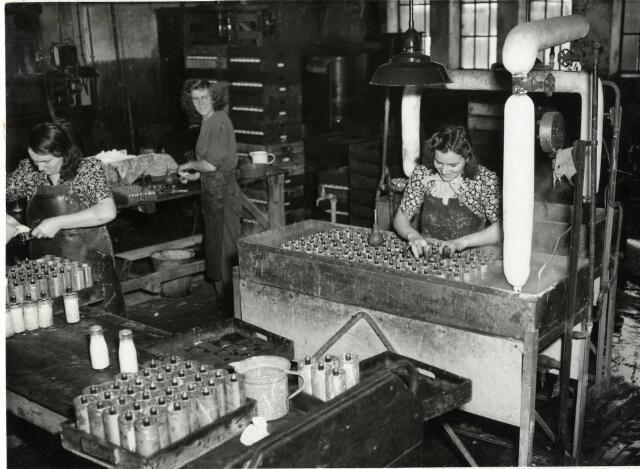 1950-1960. Interieur van de Batterijenfabriek Herberhold (Balkstraat 1-3) te Utrecht: kokerij, met links een personeelslid tijdens het gieten van het zuur in de aluminium hulzen en rechts een personeelslid die de elementen in het kookbad plaatst. Tweede van links staat Jannie van Bentum.