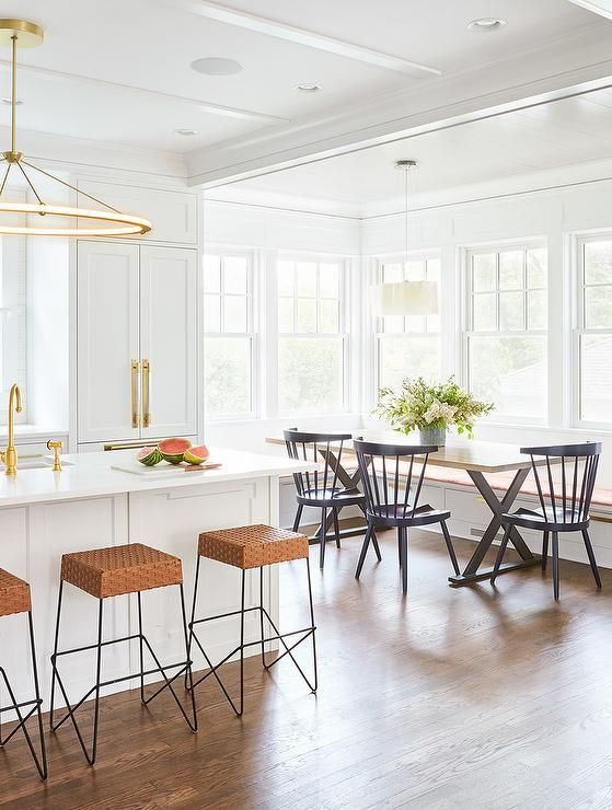 Eat in kitchen boasts a a black x-base dining table fitted with a wood top seating black windsor dining chairs and a white l-shaped banquette.
